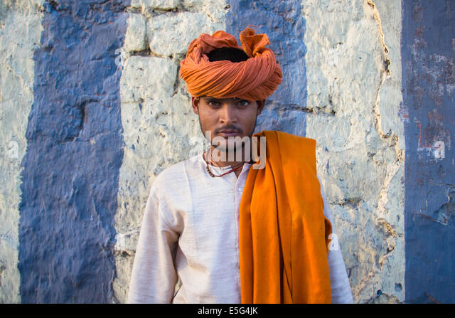 Young colorful hindu man, wearing an orange turban, posing before a striped wall in the old part of New Delhi, capital - Stock-Bilder