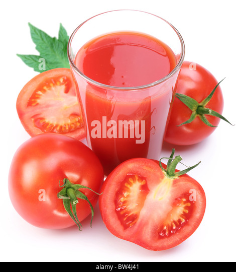 Full glass of fresh tomato juice and plants near it. - Stock Image