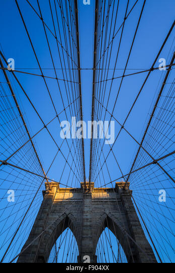 Brooklyn Bridge tower with double gothic arches and symmetrical suspension cables at sunset with clear blue sky, - Stock Image