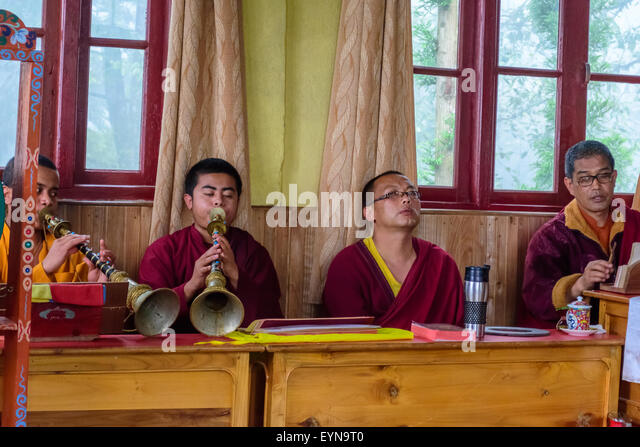 Four Buddhist priests, Lamas, praying inside a monastery in India, playing traditional flute, gong with copy space - Stock Image