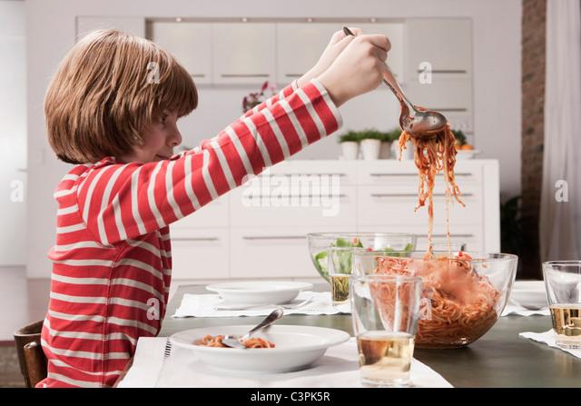 Germany, Cologne, Boy (6-7) serving spaghetti, side view - Stock-Bilder