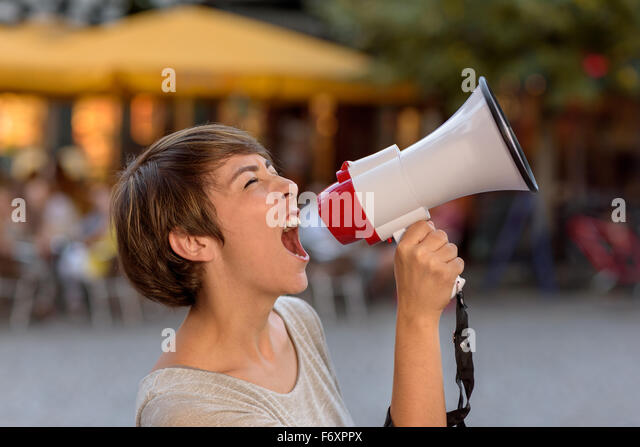 Angry young woman yelling into a megaphone as she stands on an urban street venting her frustrations during an open - Stock Image