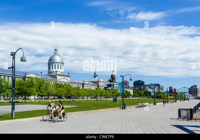 Cyclists on the riverfront promenade in the Quais du Vieux Port area with Bonsecours Market to left, Montreal, Quebec, - Stock Image