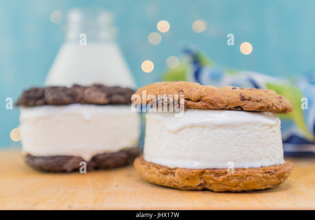 Chocolate Chip Cookie Ice Cream Sandwich in Foreground on table top - Stock Image