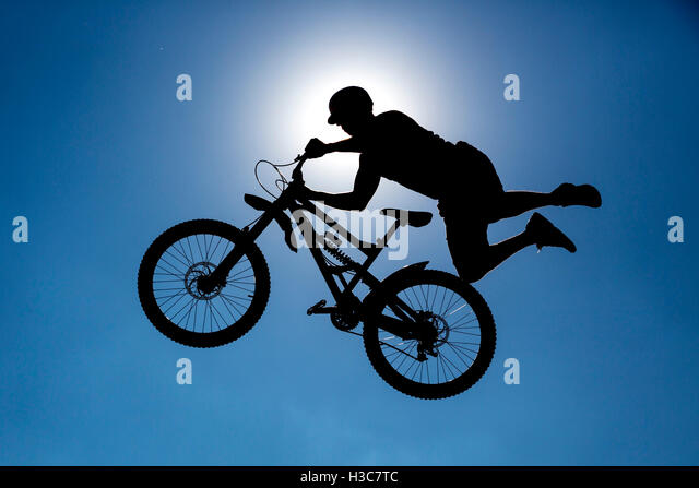 An extreme rider is making a free style jump from a ramp. The young boy with his bicycle is seen as a silhouette - Stock Image