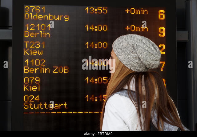 woman in front of destination board display at intercity bus station in germany - Stock-Bilder
