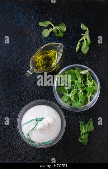 Whole tied Italian cheese burrata in brine served with fresh corn salad and olive oil in glass bowls over dark textural - Stock Image