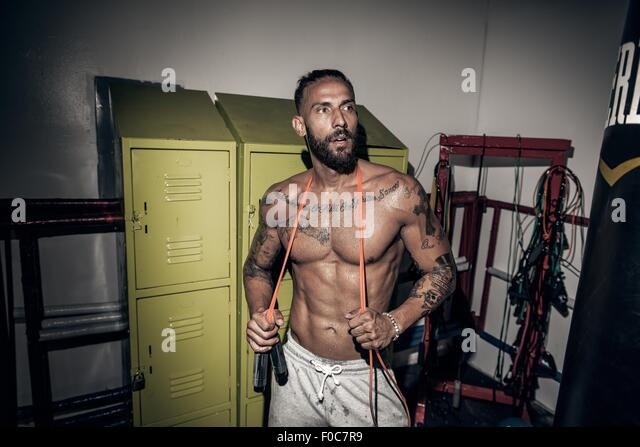 Tattooed male boxer with skipping rope in gym - Stock-Bilder