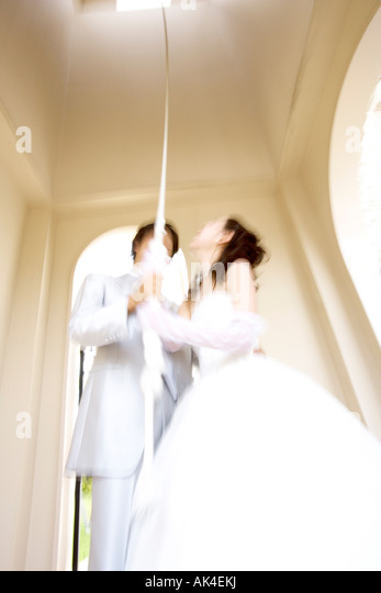 Bride and groom pulling the rope of bell - Stock-Bilder