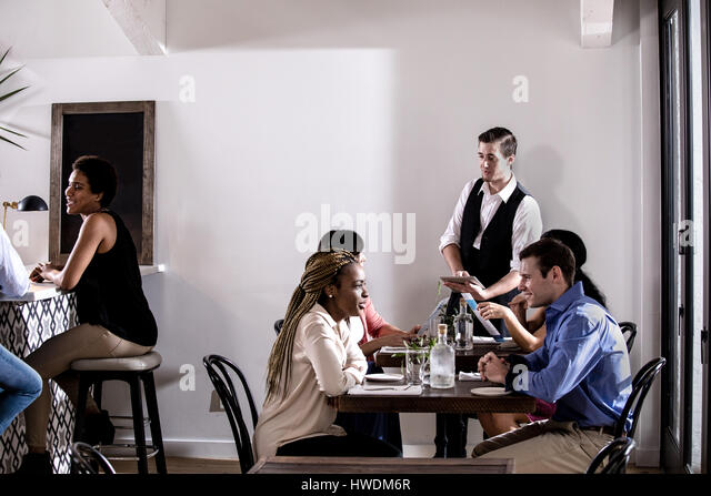 Waiter serving diners in restaurant - Stock-Bilder
