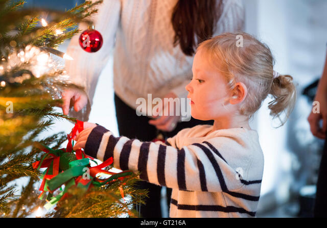Mother helping daughter in decorating Christmas tree at home - Stock-Bilder