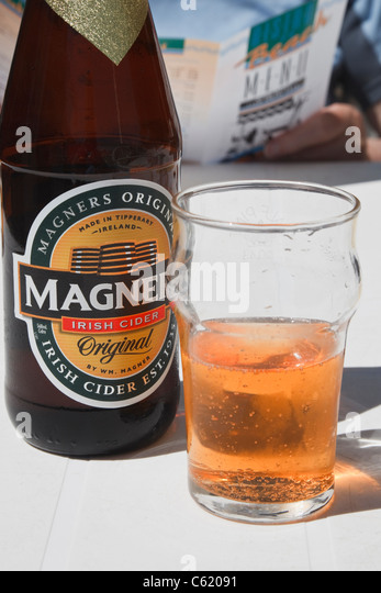 UK, Britain, Europe. A bottle of Magners Irish cider with glass half full of drink on a restaurant table outdoors. - Stock Image