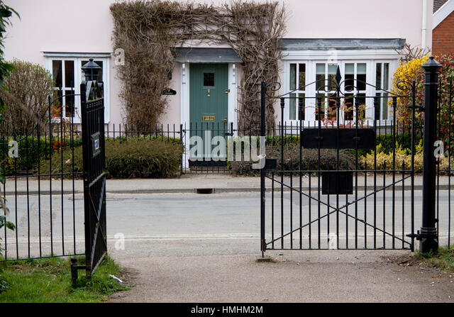 House with climber round the door seen through black metal park gates - Stock Image