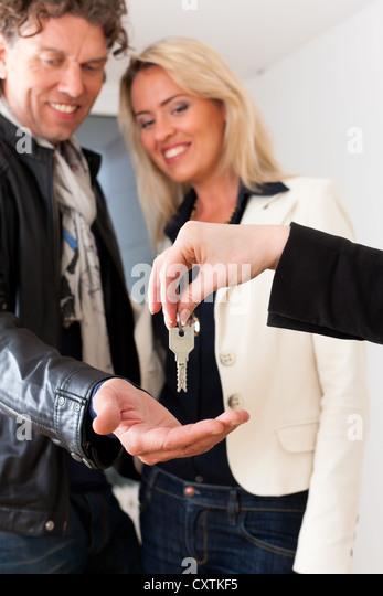Young realtor is giving the keys to an apartment to a young couple, maybe the purchaser or the tenants - Stock Image