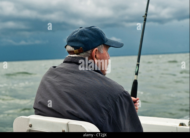 Man sport fishing from a boat. - Stock Image