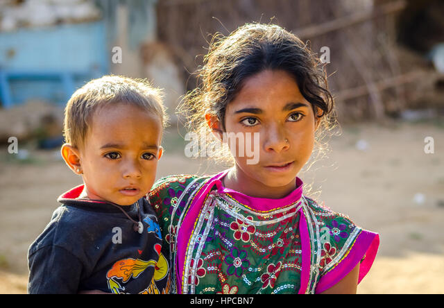 RAJASTHAN, INDIA - NOVEMBER 20, 2016: Unidentified Rajasthani poor young girl holding her brother. - Stock Image