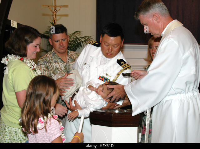 050711-N-5783F-002Pearl Harbor, Hawaii (July 11, 2005)- Lt. Cmdr. Chris Buziak holds his son during a baptism ceremony - Stock Image