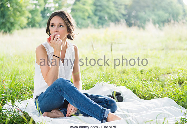 Mid adult woman sitting on picnic blanket in field eating an apple - Stock Image