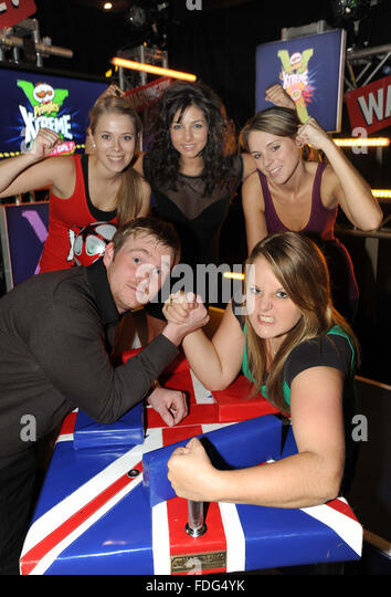 World arm wrestling champion Joanne 'The Hitwoman' Poole shows Jason Wright her strength cheered on by LtoR - Stock Image