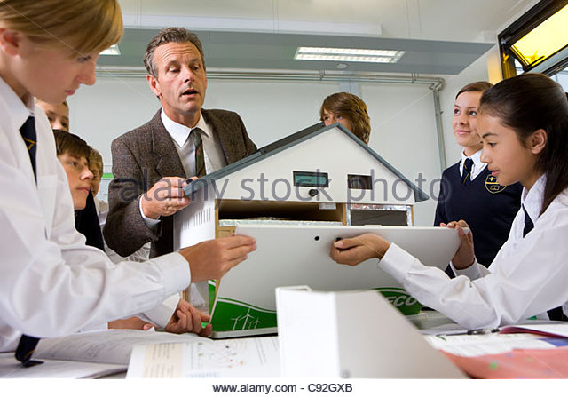 Students and teacher constructing energy efficient house in science class - Stock Image