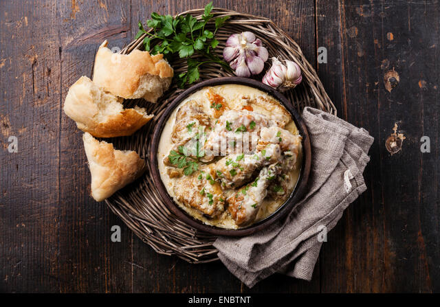 Roasted chicken with creamy garlic sauce in clay pan ketsi on dark wooden background - Stock Image