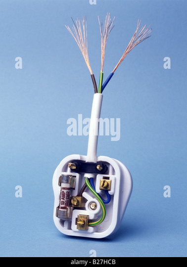 3 pin plug UK type showing copper wires and insulation blue neutral brown live green and yellow earth on blue background - Stock Image