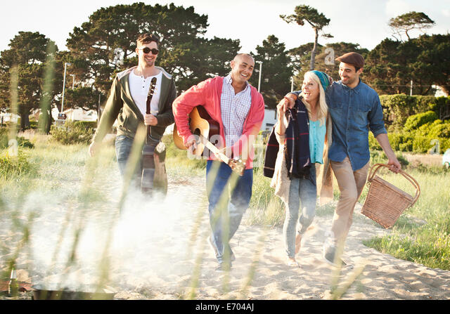 Four adult friends with acoustic guitar and picnic basket on Bournemouth beach, Dorset, UK - Stock Image