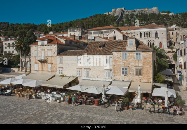Cafes in the main square overlooked by the ancient fortress, in the medieval city of Hvar, island of Hvar, Dalmatia, - Stock-Bilder