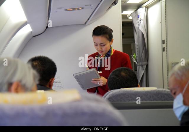 China Beijing Beijing Capital International Airport PEK Air China onboard cabin passengers Asian woman flight attendant - Stock Image