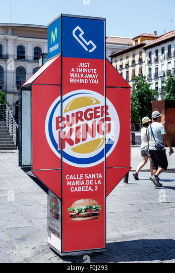 Madrid Spain Europe Spanish Atocha public phone booth advertising marketing American company Burger King brand restaurant - Stock Image