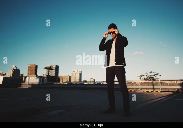 Low Angle View Of Man Wearing Sunglasses Against Clear Sky - Stock Image