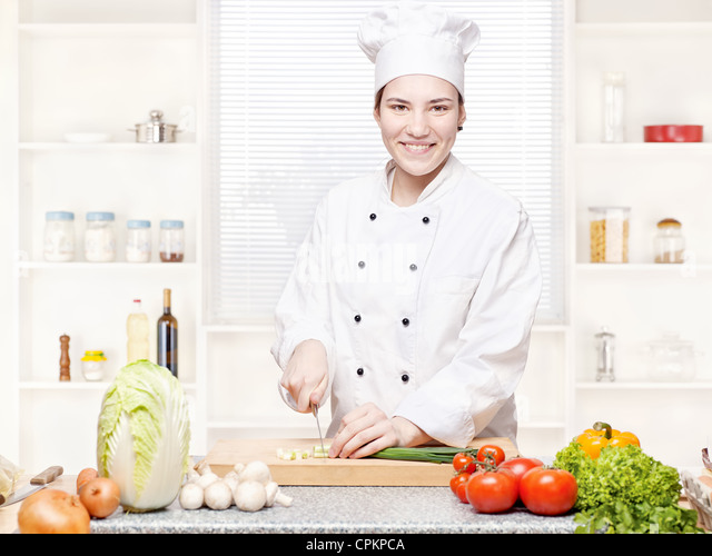 Young female chef cutting onions on the cutting board in kitchen - Stock Image