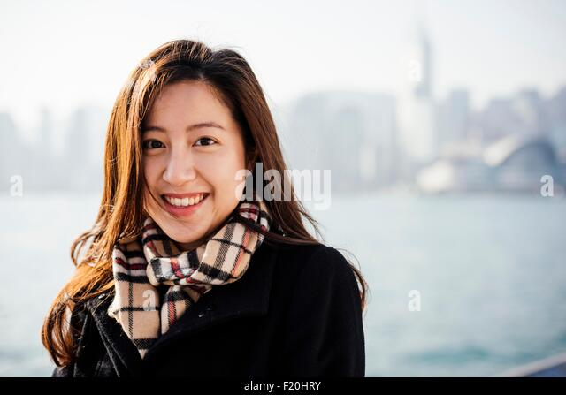Portrait of young woman wearing checked scarf in front of water, looking at camera smiling - Stock Image