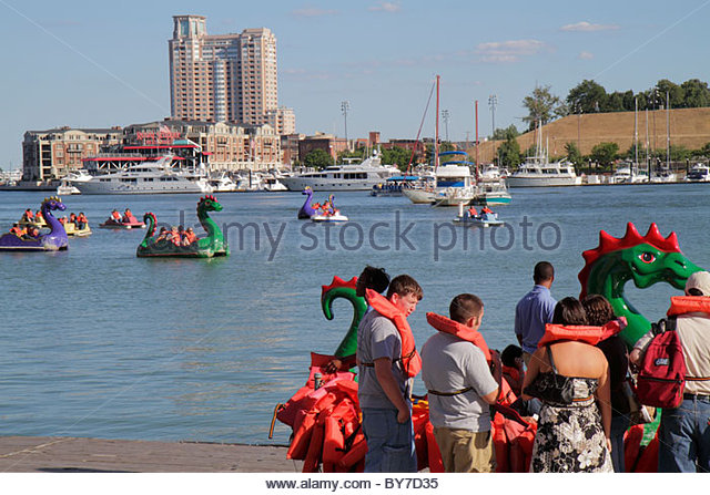 Baltimore Maryland Inner Harbor Patapsco River port waterfront Harborplace paddle boat ride dragon boat skyline - Stock Image