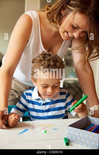 Young preschool teacher looking at what the little kid is drawing - Stock Image