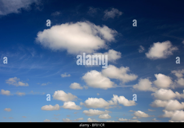 Cumulus humilis white fluffy Clouds in deep blue polarised sky - Stock Image