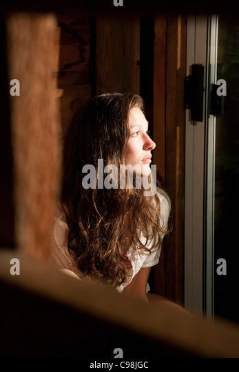 Teenage girl staring open window - Stock Image
