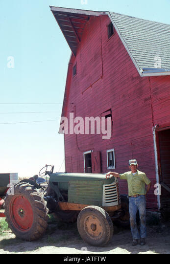 Farmer in Nebraska with an old tractor in front of a big red barn - Stock Image