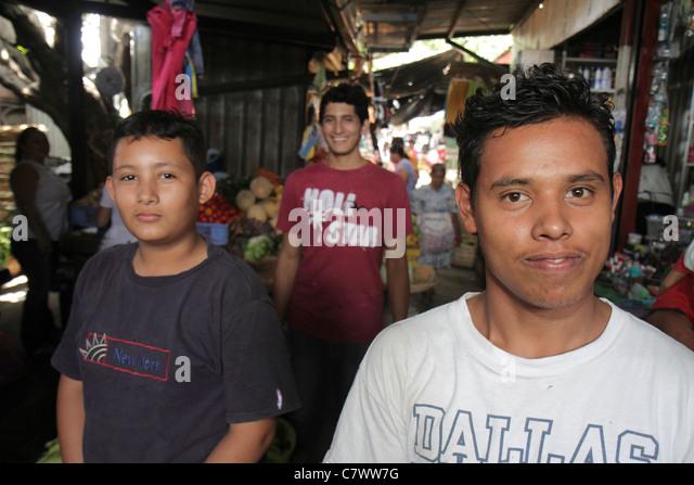 Nicaragua Managua Mercado Roberto Huembes market shopping marketplace vendor stall aisle Hispanic boy teen customer - Stock Image