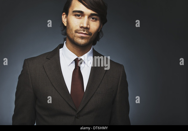 Portrait of handsome young businessman in suit looking at camera. Asian male fashion model in office attire. - Stock Image
