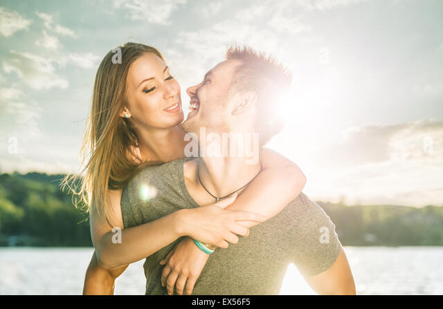 Couple in love embracing at the lake, sun flare - Stock-Bilder
