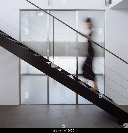 Blurred figure walking up modern metal staircase - Stock Image