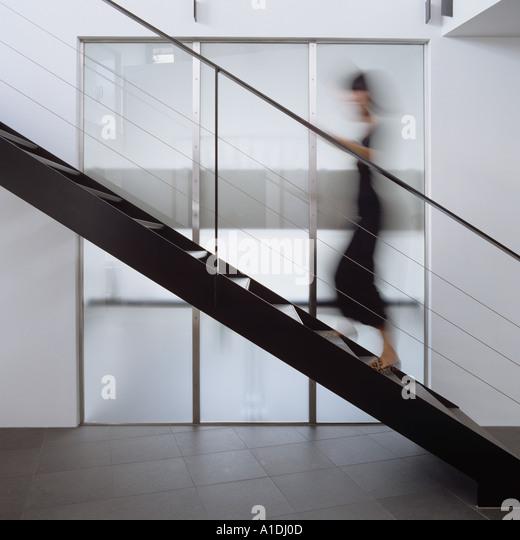 Blurred figure walking up modern metal staircase - Stock Image