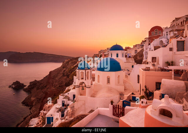 Greek church with three blue domes at sunset, Oia, Santorini (Thira), Cyclades Islands, Greek Islands, Greece, Europe - Stock Image