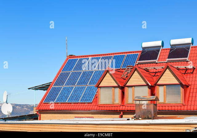 modern energy-saving technology - Solar Batteries and heaters on house roof - Stock Image