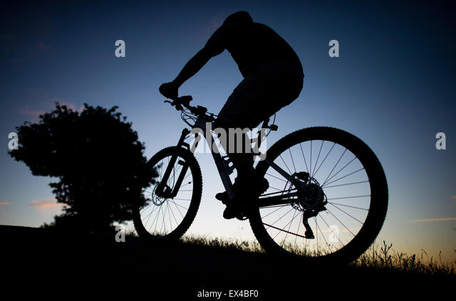 Hanover, Germany. 01st July, 2015. A man rides a bicyle during sunset on Kronsberg hill in Hanover, Germany, 01 - Stock-Bilder