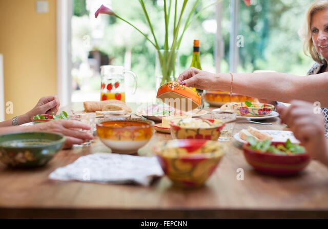 Three women having lunch together at home - Stock Image