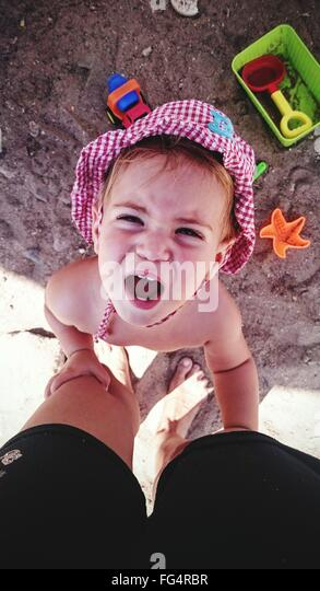 Directly Above Shot Of Girl Crying While Holding Father's Legs At Beach - Stock Image