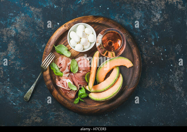 Prosciutto di Parma, cantaloupe melon, mozzarella cheese in bowl, fresh basil leaves and glass of rose wine in round - Stock Image