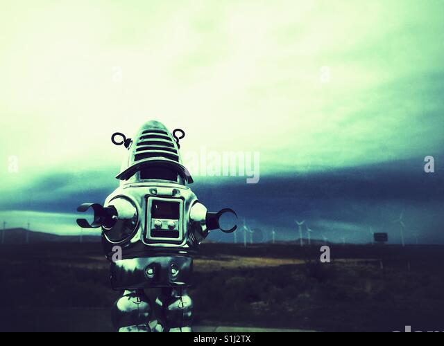 Vintage metal toy robot standing in front of the wind turbines in Eastern Washington - Stock Image